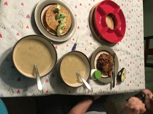 left over garlic soup with a side of chicken quesadilla or cauliflower grilled cheese with shredded pork, rice and beans for the kids on a messy dinner table